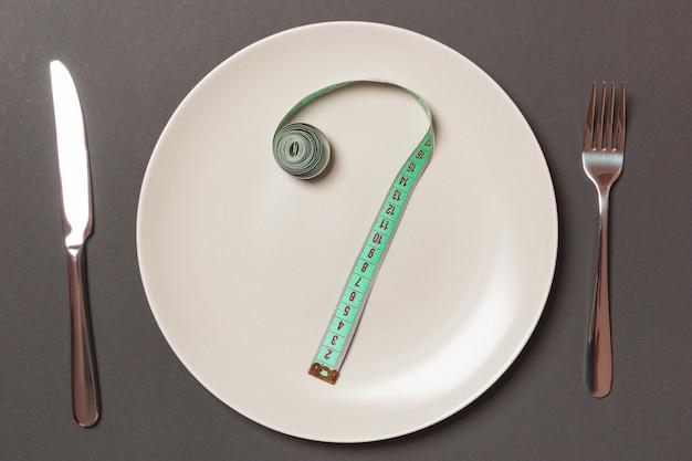 Forchetta e piatto con metro a nastro su sfondo colorato. concetto di dieta