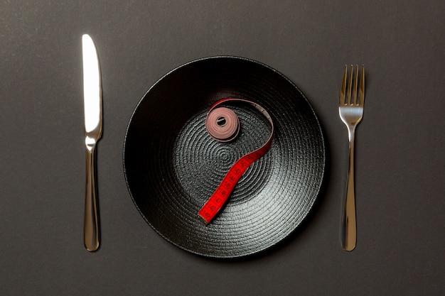Forchetta e piastra con metro a nastro sul colore. concetto di dieta