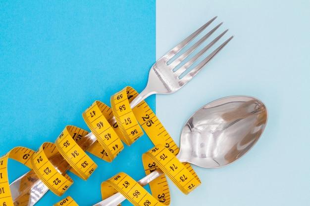 La forchetta e il cucchiaio sono infilati da un nastro per la misurazione