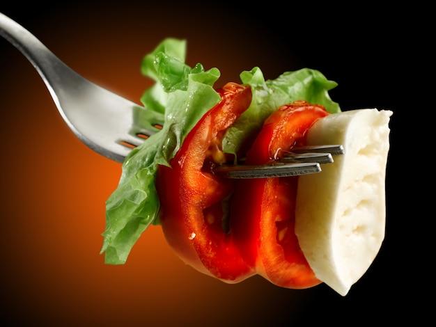Forchetta con pomodoro mozzarella e insalata