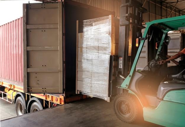 Autista del carrello elevatore che carica pallet di carichi pesanti nel camion del contenitore di spedizione.