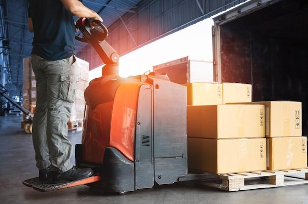 Autista del carrello elevatore che carica le scatole dei pacchi nel contenitore di carico al servizio di consegna del magazzino portuale