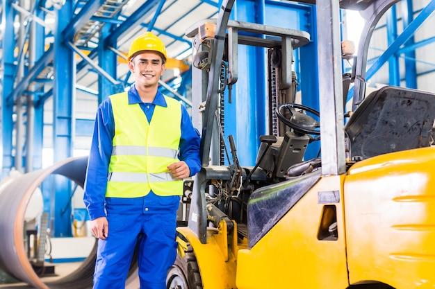 Autista del carrello elevatore in piedi orgoglioso nello stabilimento di produzione