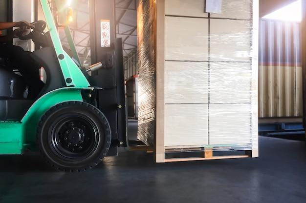 Il trattore del carrello elevatore carica le scatole del pacchetto nel contenitore di carico al servizio di consegna del magazzino della banchina