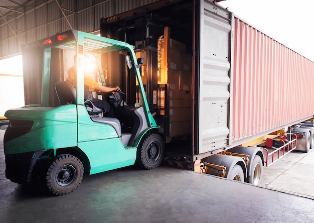 Trattore carrello elevatore che carica le scatole del pacchetto nel trasporto di logistica del magazzino del contenitore di carico di spedizione
