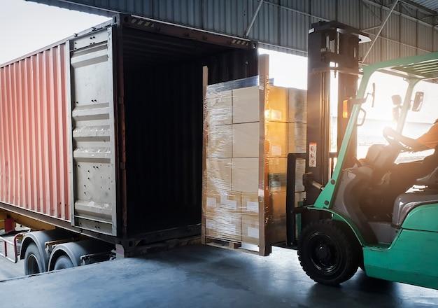 Trattore del carrello elevatore che carica le scatole del pacchetto nel trasporto di logistica del magazzino del contenitore di carico di spedizione