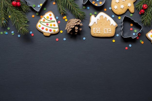 Moduli per cucinare e biscotti di natale su sfondo nero