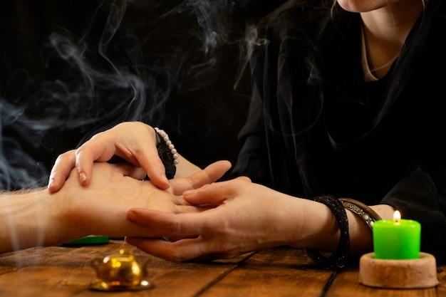 Un indovino o un oracolo alla ricerca delle linee del destino nel palmo di una persona