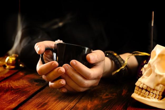 Indovino o oracolo con una tazza nera in mano per predire la fortuna sui fondi di caffè. letture psichiche e concetto di chiaroveggenza