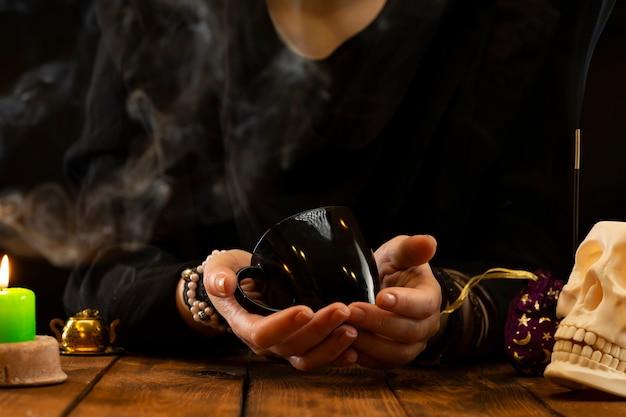 Indovino o oracolo con in mano una tazza nera per predire il futuro sui fondi di caffè