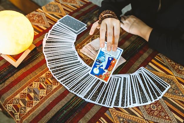 Indovino che usa le carte dei tarocchi e i soldi tailandesi sullo sfondo del tavolo