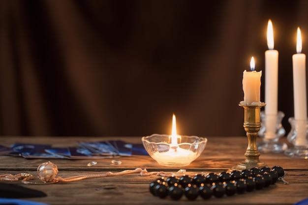 Cartoline di indovino e candele accese su un tavolo di legno su sfondo marrone scuro