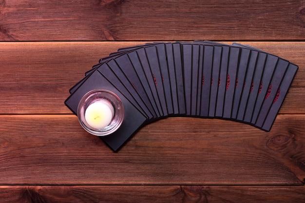 Cartoline di predizione della fortuna su un tavolo di legno con una candela con posto per il testo. concetto di divinazione, carte dei tarocchi, sensitivo.