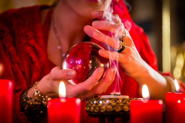 Cartomante o oracolo esoterico, vede il futuro guardando nella loro sfera di cristallo, incenso che brucia e candele che danno luce