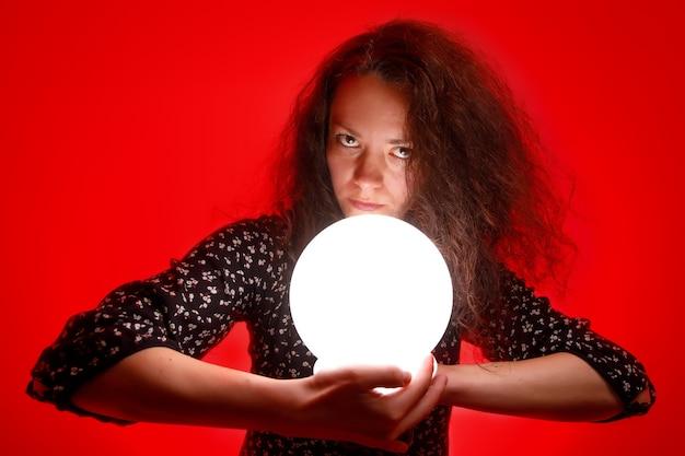 Cartomante in possesso di una palla incandescente nelle sue mani. muro rosso.
