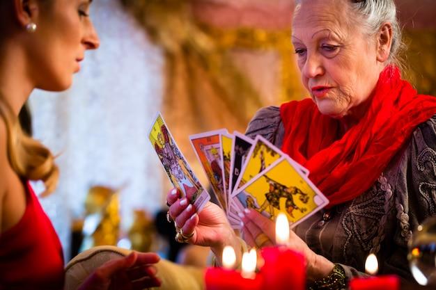 Fortuneteller che posa le carte dei tarocchi con il cliente Foto Premium