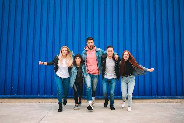 Inoltrare. un gruppo di quattro giovani amici diversi in abito di jeans sembrano spensierati, giovani e felici camminando per le strade della città. moda di abiti urbani, libertà, amicizia, concetto di stile.