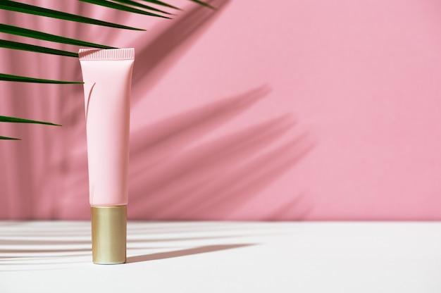 Fondazione in un tubo di plastica rosa su sfondo bianco, rosa con foglie e ombra di una palma tropicale. accessorio cosmetico femminile per trucco, tinta, fluido. mockup, identità, copia spazio.