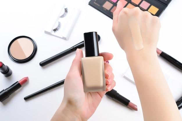 Fondazione nelle mani della donna. prodotti per il trucco professionale con prodotti cosmetici di bellezza, fondotinta, rossetto, ombretti, ciglia, pennelli e strumenti.