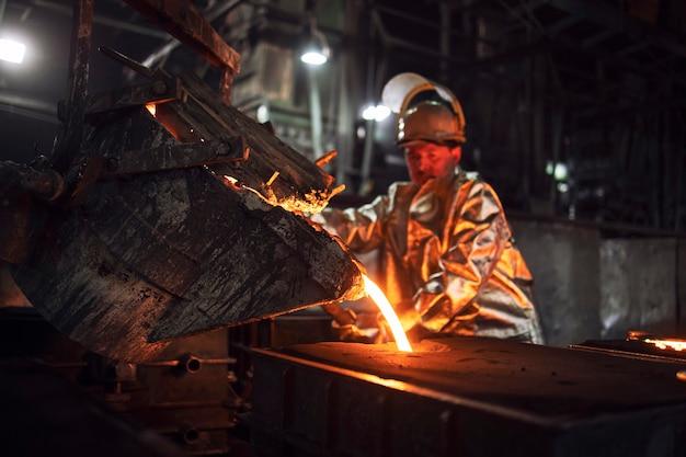 Gente che lavora sodo nella fonderia che versa ferro liquido caldo dal secchio negli stampi, nella produzione di minerale di ferro e nella metallurgia.