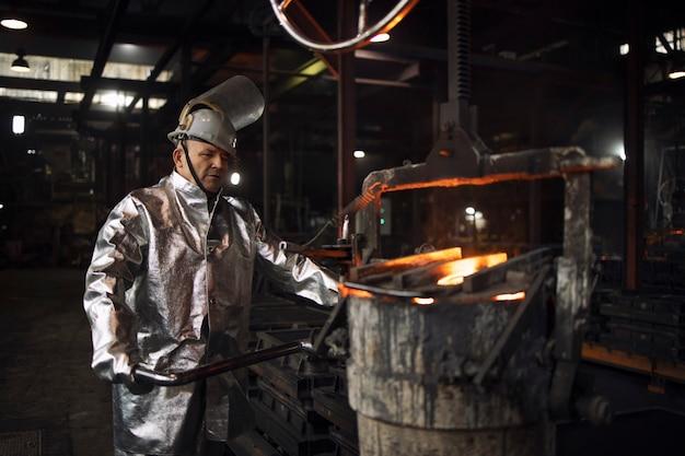Operaio di fonderia pronto a versare ferro liquido in stampi, fonderia e produzione acciaio.