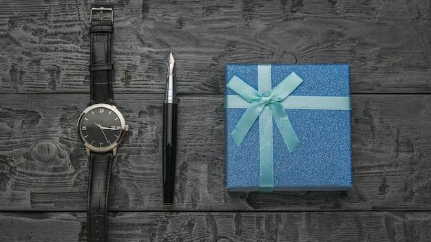 Una penna stilografica, un orologio da uomo e una confezione regalo blu su un collo di legno
