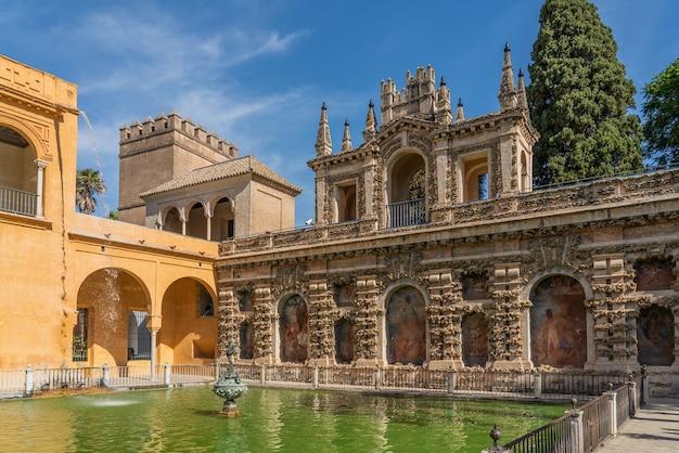 La fontana con l'edificio storico con la pittura nel cortile dei palazzi real alcazar di siviglia, in andalusia, spagna