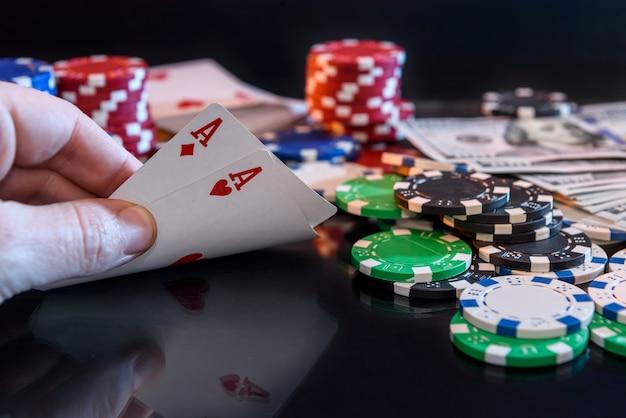 Quattro assi in mano e gettoni da gioco sul nero