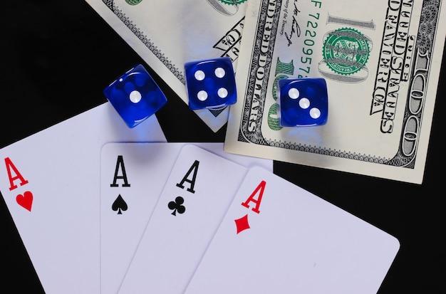 Quattro assi con dadi e banconote da cento dollari su una superficie nera. gioco d'azzardo