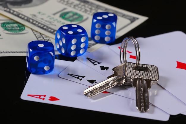 Quattro assi con dadi e banconote da cento dollari con le chiavi di casa su una superficie nera. è in gioco tutto. gioco d'azzardo