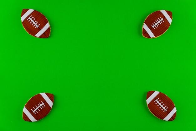 Quattro palloni da football americano isolati su sfondo verde. vista dall'alto.