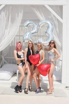 Quattro ragazze attraenti che riposano al bar della spiaggia, bevono un cocktail rinfrescante, ridono e si divertono. i costumi da bagno luminosi e gli occhiali da sole.