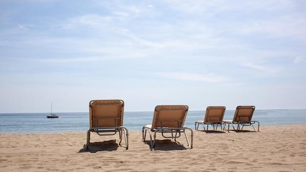 Quattro sedie a sdraio sulla spiaggia