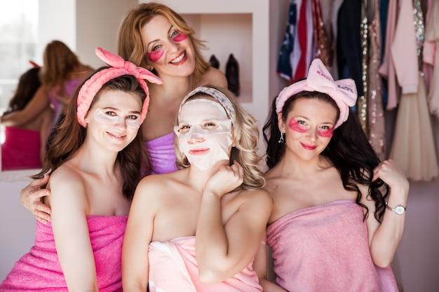 Quattro belle giovani donne posano con le toppe sotto gli occhi e in una maschera cosmetica in tessuto