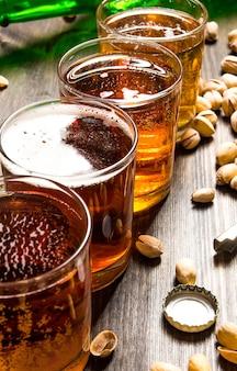 Quattro birre con pistacchi su un tavolo di legno.