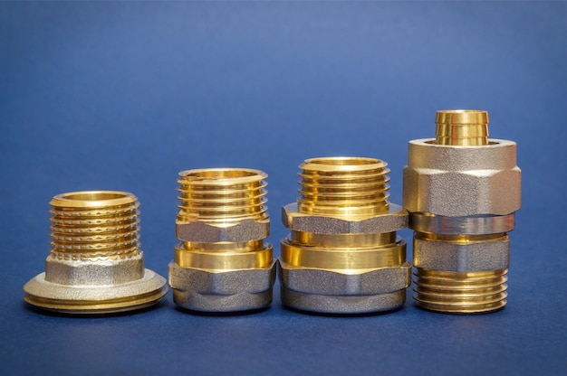 Quattro raccordi in ottone vengono spesso utilizzati per il collegamento di installazioni di acqua e gas su sfondo blu