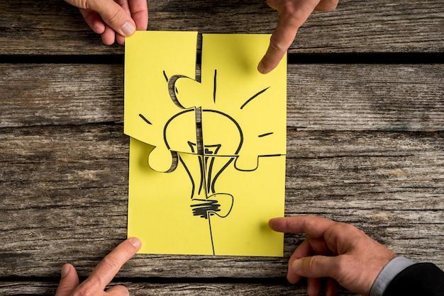Quattro genti di affari che tengono i pezzi di un puzzle che porta l'immagine di una lampadina concettuale di brainstorming o lavoro di squadra.