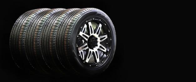 Quattro ruote auto in gomma con cerchio in lega isolato sul muro nero, copia dello spazio
