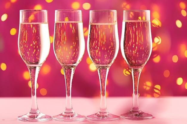 Quattro bicchieri di champagne su sfondo rosa con luci sfocate della ghirlanda