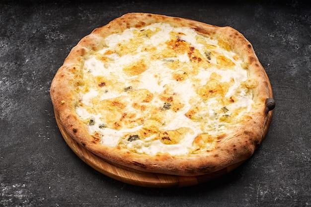 Pizza al formaggio quattro su una tavola di legno chiaro, su uno sfondo di cemento scuro