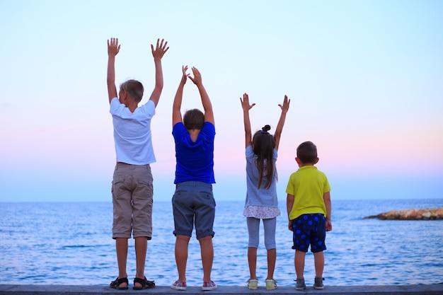 Quattro figli sulla vocazione della spiaggia la giovane famiglia in vacanza si diverte molto