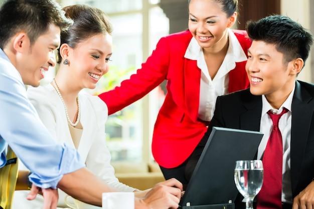Quattro uomini e donne asiatici cinesi di affari che hanno riunione nella hall di un hotel che esamina i documenti sul computer portatile e che bevono caffè