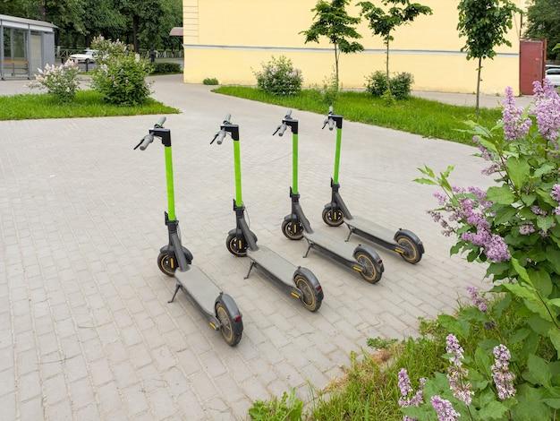 Quattro scooter da città sull'asfalto. quattro scooter parcheggiati nella città estiva. moderno mezzo di trasporto giovanile.