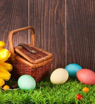 Quattro uova di pasqua colorate decorate in erba con fiori tulipani e cestino da picnic.