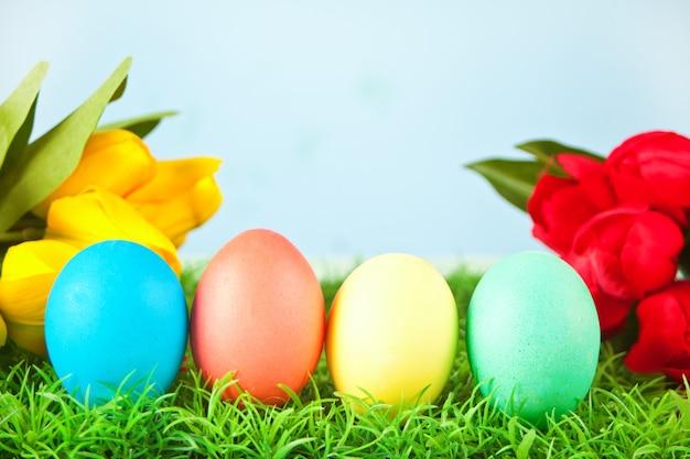 Quattro uova di pasqua decorate in erba con fiori tulipani sullo sfondo.