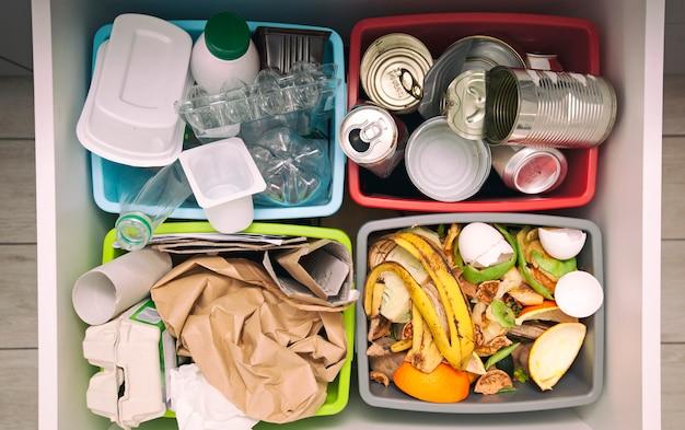 I quattro diversi contenitori per lo smistamento dei rifiuti. per plastica, carta, metallo e rifiuti organici