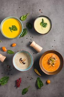 Quattro diverse gustose minestre decorate con erbe aromatiche. vista dall'alto