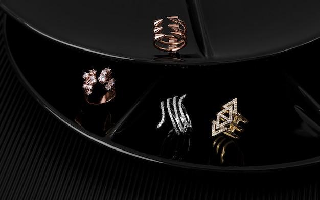 Quattro diversi tipi di anelli d'oro su piatti neri da esposizione
