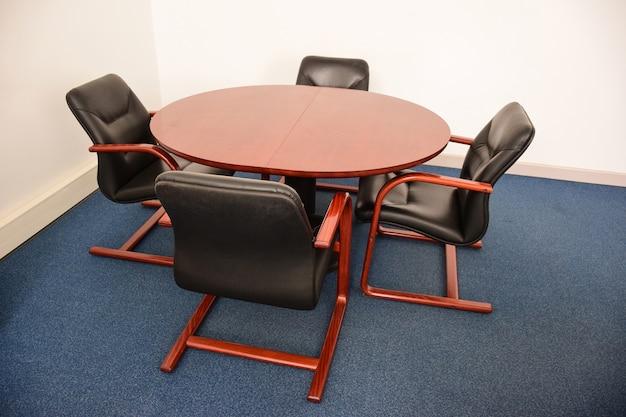 Quattro sedie da ufficio decorative in pelle vuote siedono intorno a una tavola rotonda marrone.