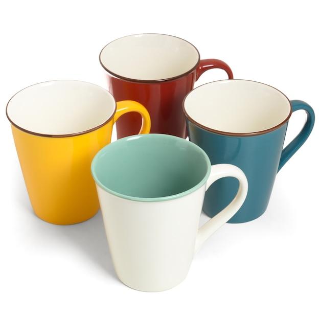 Quattro tazze di ceramica multicolori vuote su bianco